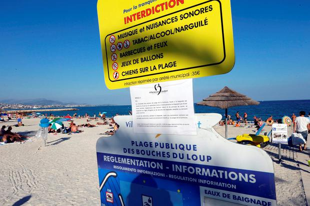 A bylaw forbidding women to wear burkini is posted on an information panel at a public beach in Villeneuve-Loubet, French Riviera, southern France. Photo: AP Photo/Claude Paris