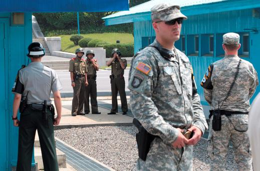 North Korean army soldiers watch the south side while a South Korean and United States Army soldiers stand guard at the border villages of Panmunjom in Paju, South Korea. (AP Photo/Ahn Young-joon, File)