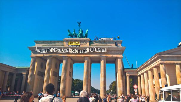 Anti-Islam activists have staged an hour-long demonstration atop Berlins Brandenburg Gate. (AP Photo Frank Jordans)