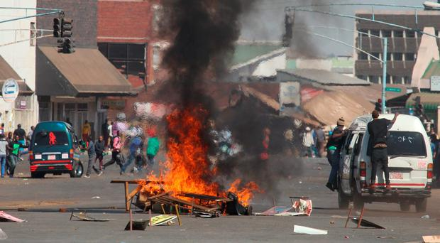 A fire burns in the street, set by protestors during a demonstration in Harare (AP Photo/Tsvangirayi Mukwazhi)