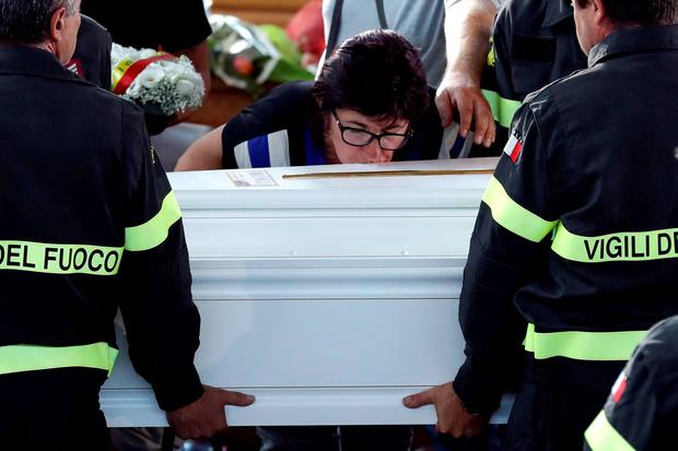 A woman kisses the coffin of 9-year-old Giulia Rinaldo, as it is carried outside the gymnasium at the end of the state funeral service in Ascoli Piceno, Italy (AP Photo/Andrew Medichini)
