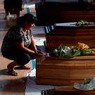 TEARS: A woman touches a coffin of one of the victims of Wednesday's earthquake inside a gymnasium in Ascoli Piceno. Italy yesterday observed a day of national mourning as many victims were buried. Photo: Gregorio Borgia/AP