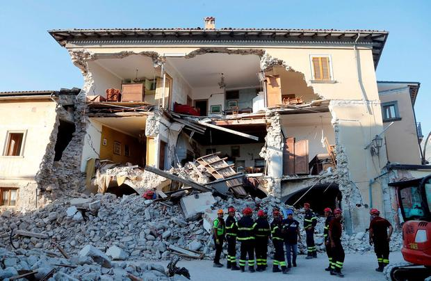 Firefighters stand next to a collapsed house following an earthquake in Amatrice, central Italy. REUTERS/Ciro De Luca