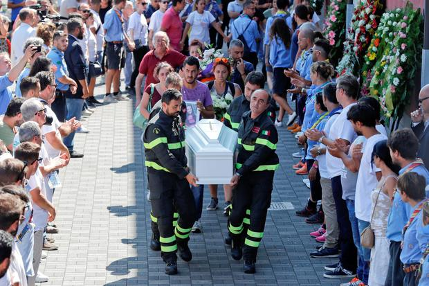 The coffin of 9-year-old Giulia Rinaldo, is carried outside the gymnasium at the end of the state funeral service in Ascoli Piceno. (AP Photo/Gregorio Borgia)