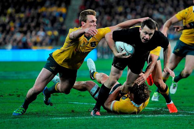 New Zealand's Ben Smith is tackled by Australia's Dane Haylett-Petty and Michael Hooper. Photo: Marty Melville/AFP/Getty Images