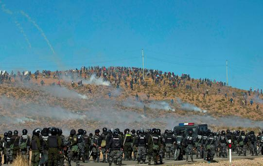 Independent miners, above, clash with the police as they run from clouds of tear gas during protests in Panduro, Bolivia. (AP Photo/Juan Karita)