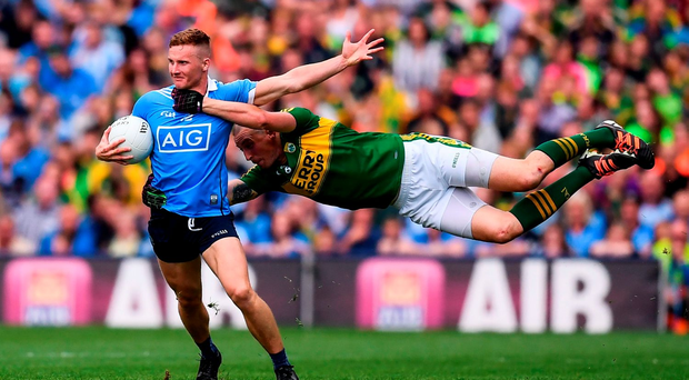 Kerry's Kieran Donaghy is in full flight as he attempts to stop the charge of Dublin's Ciaran Kilkenny. Photo: Sportsfile