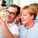 Angela Merkel (right) poses for a selfie with a visitor during the German government's open day at the Chancellery in Berlin. Photo: Getty Images