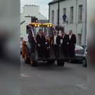 Ronan Waldron and his groomsmen arrive to his wedding harnessed to the bucket of a JCB. Photo: Colleen Waldron