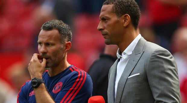 Ryan Giggs speaks with Rio Ferdinand ahead of a Manchester United match last season. Getty
