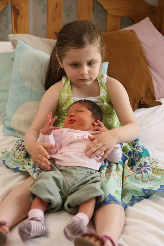 Megan, aged five, with her then newborn sister Hannah