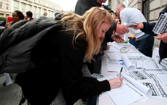 Jan Boland signs a petition outside the GPO calling on the government to spend Apple's €13bn on housing. Photo:Rollingnews.ie