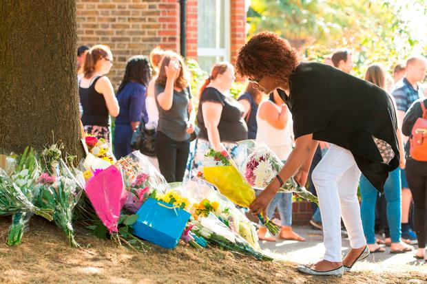 People lay flowers Lennard Road in Penge, south-east London, where a car being chased by police ploughed into a family leaving two people dead