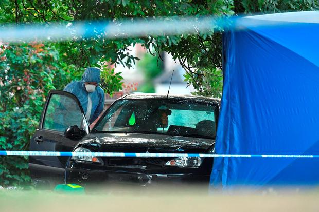 A forensic police officer examines a car at the scene in Lennard Road, Penge in south-east London after a car being chased by police has ploughed into a family leaving two people dead
