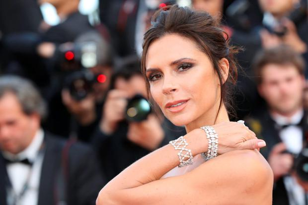 British fashion designer Victoria Beckham poses as she arrives on May 11, 2016 for the opening ceremony of the 69th Cannes Film Festival