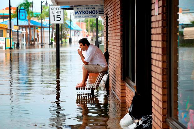 Pedro Muacaj rests on higher ground in front of a gift shop along a flooded section of Dodecanese Blvd. in Tarpon Springs, Fla