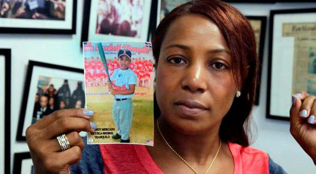 Maribel Martinez holds a photo of her son Andy at her attorney's office