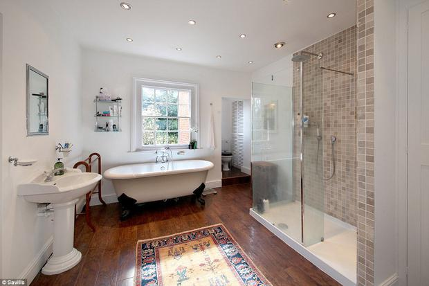 The period-style bathroom features a stand-alone bath