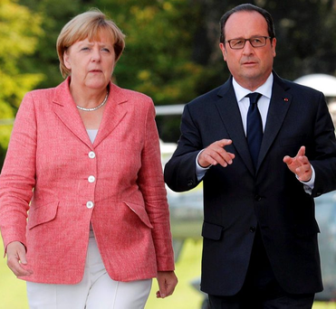 French President Francois Hollande welcomes German Chancellor Angela Merkel as she arrives for a meeting in Evian, France, yesterday Photo: Reuters/Philippe Wojazer