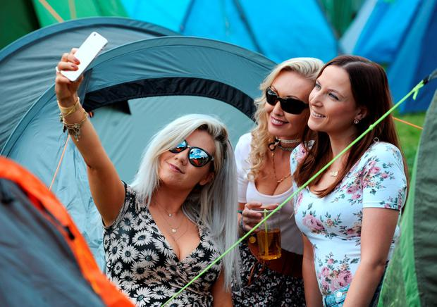 Girls take a selfie at their tent Photo: Caroline Quinn