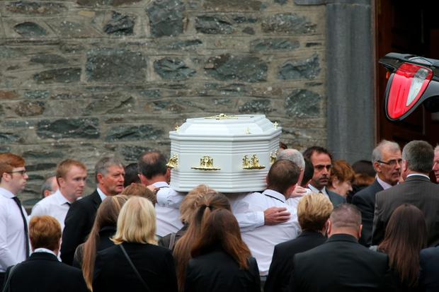A white coffin is brought into the church by mourners