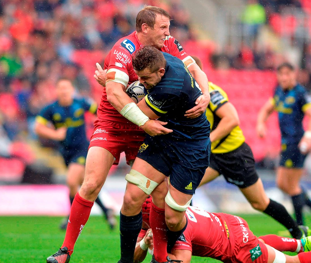 Munster's Dave Foley is tackled by Scarlets' Hadleigh Parkes. Photo: Huw Evans/Sportsfile