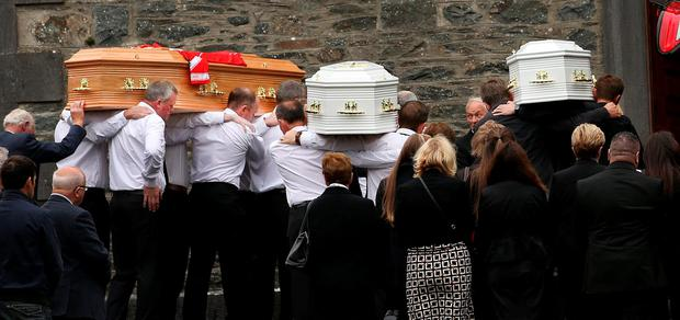 Awful day: Alan Hawes' remains are taken into the church for the funeral mass, followed by those of two of his sons Photo: Gerry Mooney
