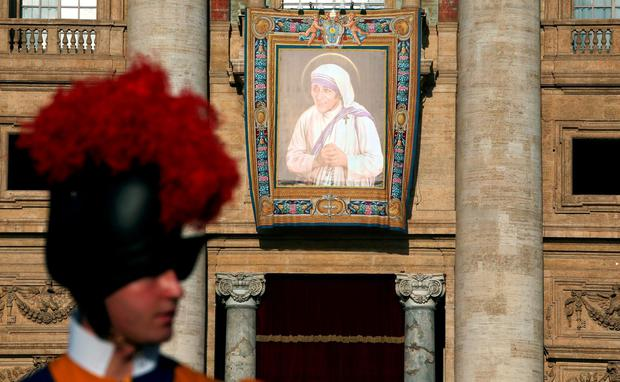 A Swiss Guard stands in front of a tapestry depicting Mother Teresa of Calcutta before a mass celebrated by Pope Francis for her canonisation in Saint Peter's Square at the Vatican September 4, 2016