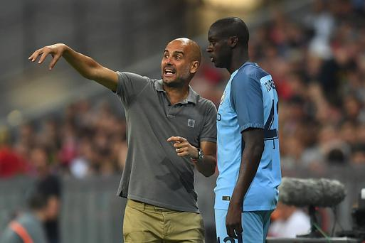Pep Guardiola speaks with substitute Yaya Toure of Manchester City