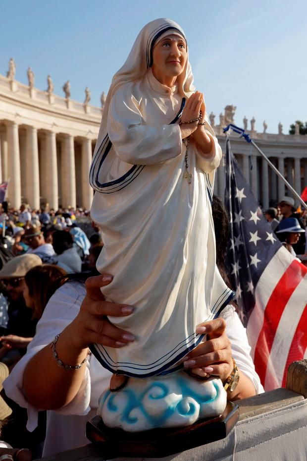 A member of the congregation holds a statue of Mother Teresa in St Peter's Square. (AP Photo/Gregorio Borgia)