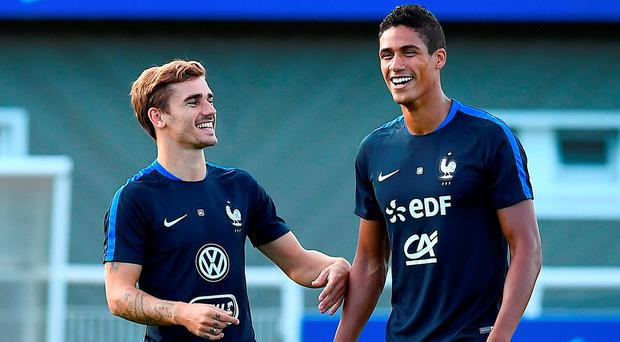 France's forward Antoine Griezmann (L) jokes with France's defender Raphael Varane during a training session in Clairefontaine-en-Yvelines, near Paris
