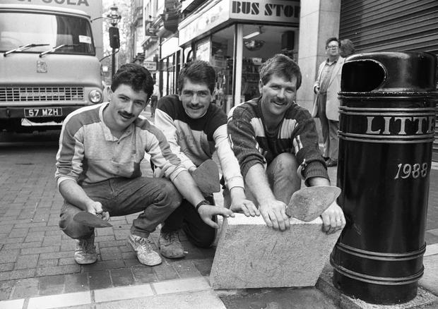 The last granite slab being laid in Grafton St, put into place by Nicky Whelan, left, and brothers Vincent, centre, and Damien McConnell of Ridgedale Construction who paved the street.