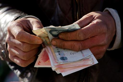 A vegetable vendor counts his money at a market in Beijing, China. Photo: Reuters