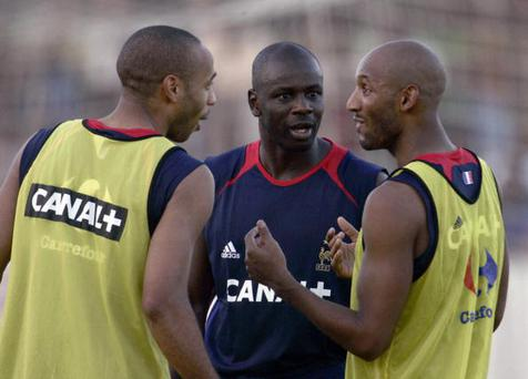 Fort-de-France, FRANCE (MARTINIQUE): French national football team striker Thierry Henry (L)and Nicolas Anelka (R) speaks with their teammate, defender Lilian Thuram, 08 November 2005 at the Dillon stadium, outside Fort de France, on the French West Indies island of La Martinique, during a training session, on the eve of a friendly match against Costa Rica. AFP PHOTO PASCAL PAVANI (Photo credit should read PASCAL PAVANI/AFP/Getty Images)