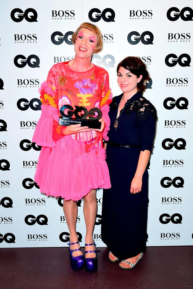 Caitlin Moran (right) presents Grayson Perry with the award for Best Writer in the press room at the GQ Men of the Year Awards 2016 in Association with Hugo Boss held at The Tate Modern in London