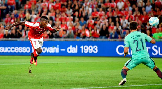 Switzerland's forward Breel Embolo (L) heads in his team's first goal. Photo: Getty