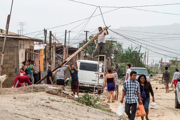 Residents of an impoverished neighbourhood raise a power line damaged in the aftermath of Hurricane Newton in Los Cabos, Mexico, September 6, 2016. REUTERS/Fernando Castillo