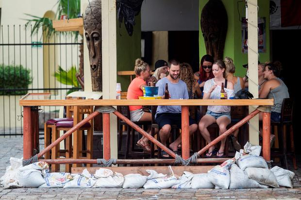 Tourists have a beer at a bar using sand bags to protect from floodwaters in the aftermath of Hurricane Newton in Los Cabos, Mexico, September 6, 2016. REUTERS/Fernando Castillo