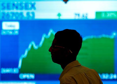 A man looks at a screen displaying news of markets update inside the Bombay Stock Exchange (BSE) building in Mumbai, India