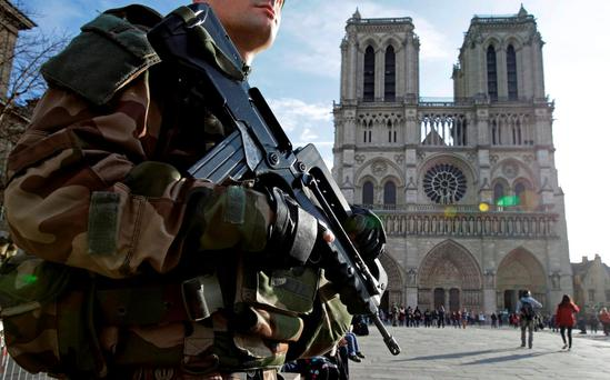 A French soldier patrols in front of Notre Dame ­Cathedral in Paris. Photo: Philippe Wojazer/Reuters