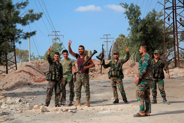 Troops loyal to Syrian President Bashar al-Assad celebrate after retaking an area of Aleppo that had been captured by rebels. Photo: Reuters