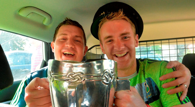 Tipperary hurlers Darren Gleeson, left, and Noel McGrath sit inside a Garda car with the Liam McCarthy Photo: Piaras Ó Mídheach/Sportsfile