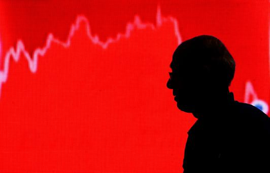 A man looks at a screen displaying news of markets update inside the Bombay Stock Exchange (BSE) building in Mumbai. Photo: Reuters