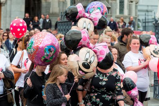 Mourners with Mickey Mouse Baloons at the church. Photo: Colin O'Riordan