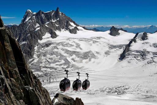 This file photo taken on August 5, 2015 shows the Panoramic Mont-Blanc cable car linking the Aiguille du Midi peak to the Helbronner peak in Italy, above the seracs and crevasses of the Glacier des Géants (Glacier of the Giants)