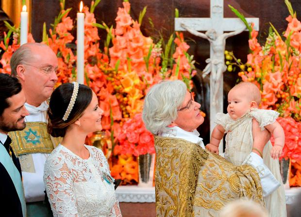 Arch Bishop Antje Jackelen holds up Prince Alexander at Palace Chapel in Drottningholm Palace in Stockholm while Prince Carl Philip (L), Bishop Johan Dalman and Princess Sofia watch during the christening of the five month-old Prince