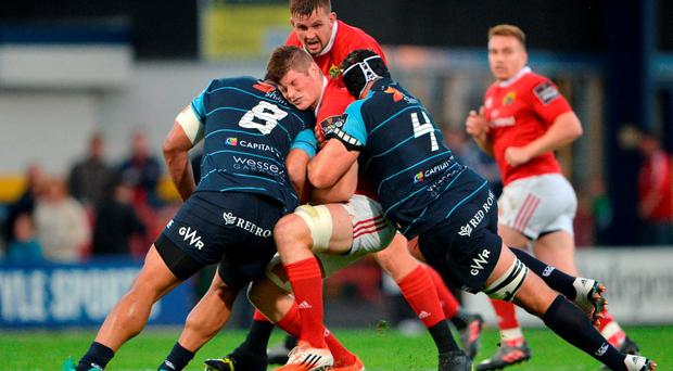 Jack O'Donoghue of Munster is tackled by Nick Williams, left, and George Earle of Cardiff Blues during the Guinness PRO12 Round 2 match between Munster and Cardiff Blues at Irish Independent Park in Cork. Photo by Piaras Ó Mídheach/Sportsfile