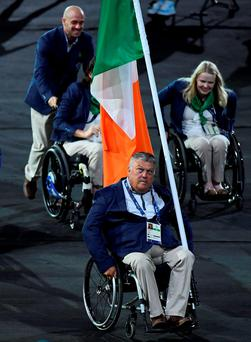 John Twomey carries the flag at the opening ceremony. Photo: Sportsfile