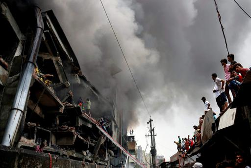 People look at a fire at a garment packaging factory outside Dhaka, Bangladesh, September 10, 2016. REUTERS/Mohammad Ponir Hossain