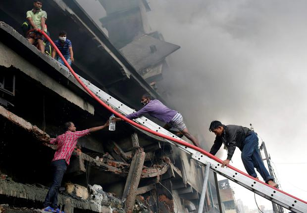 People try to extinguish a fire at a garment packaging factory outside Dhaka, Bangladesh, September 10, 2016. REUTERS/Mohammad Ponir Hossain